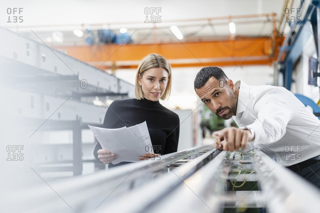 Businessman and woman with papers examining metal rods in factory hall