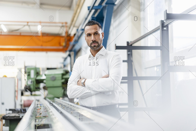 Businessman standing at metal rod in factory hall
