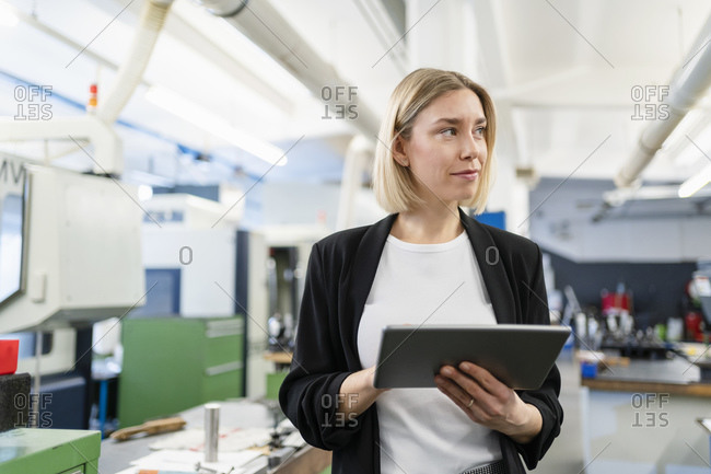 Woman holding tablet in factory hall looking around