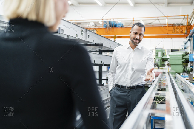 Smiling businessman and woman at metal rods in factory hall