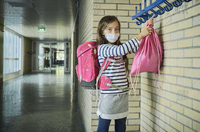 Girl wearing mask in school hanging up pouch
