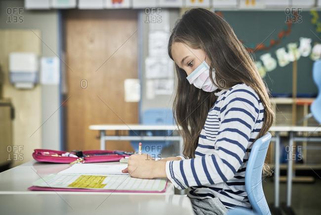 Girl wearing mask in classroom writing in workbook
