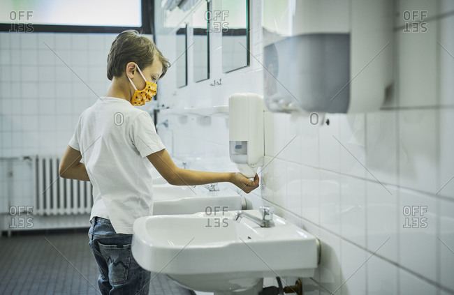 Boy wearing mask on school toilet washing his hands
