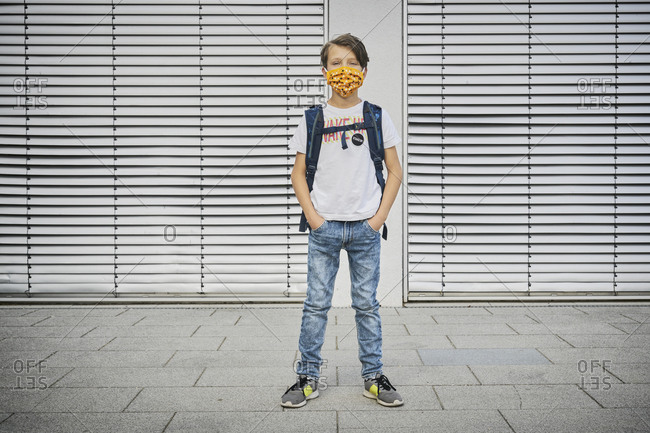 Boy with schoolbag wearing mask standing in front of building