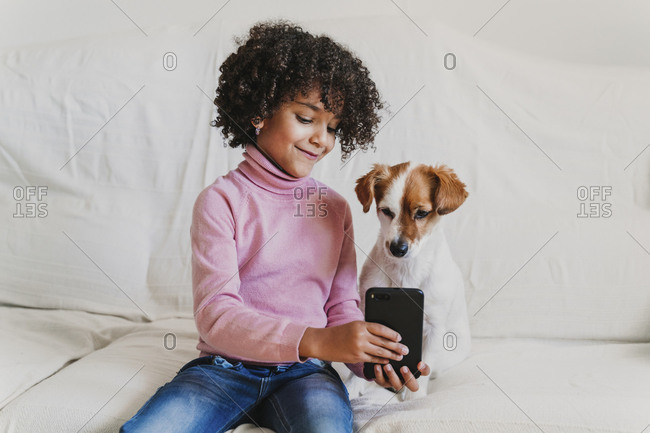 Portrait of smiling little girl sitting on the couch with her dog taking selfie with smartphone
