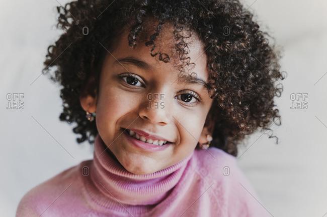 Portrait of smiling little girl wearing pink turtleneck pullover