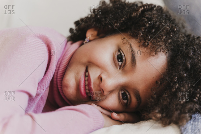 Portrait of smiling little girl wearing pink turtleneck pullover lying on couch