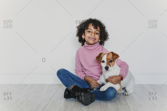 Portrait of smiling little girl sitting on the floor with her dog