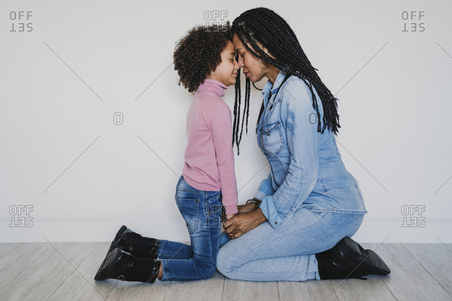 Mother and her little daughter head to head kneeling on the floor with eyes closed
