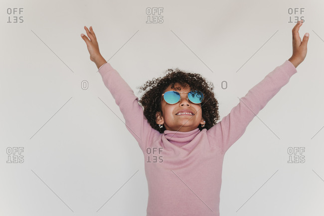 Portrait of happy little girl wearing pink turtleneck pullover and mirrored sunglasses