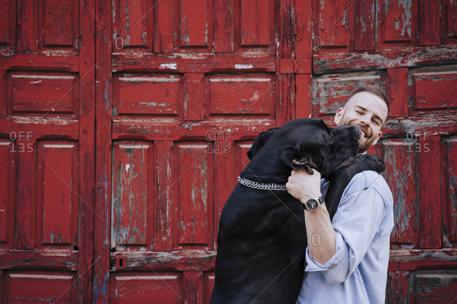 Portrait of laughing young man and his dog in front of an old red wooden door