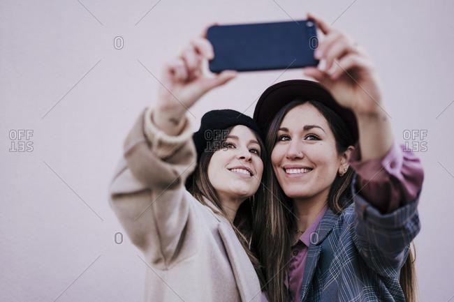 Portrait of two happy women taking selfie with smartphone