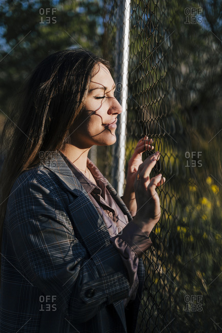 Portrait of woman standing at wire mesh fence enjoying evening twilight