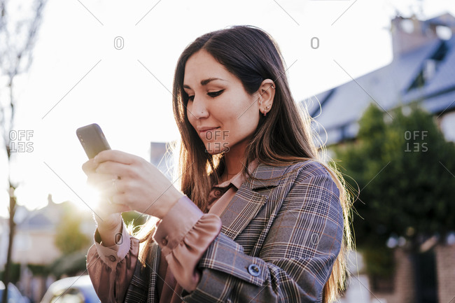 Portrait of woman looking at cell phone at backlight