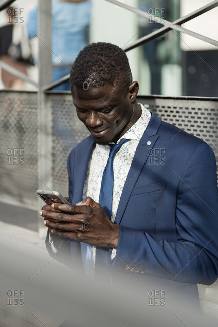 Smiling young businessman looking at cell phone