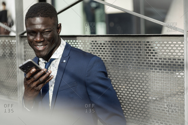 Portrait of smiling businessman using mobile phone