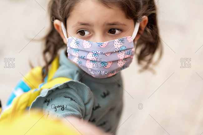 Girl with mask holding father's hand outdoors