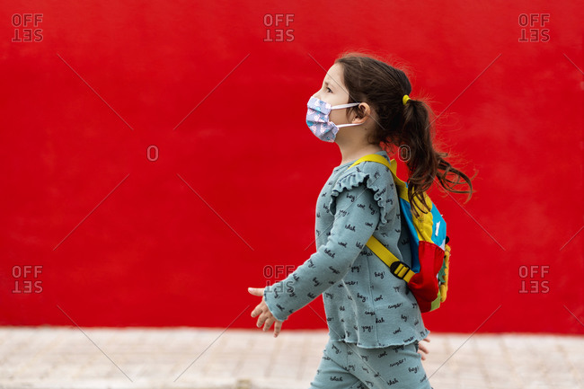 Girl walking with backpack and mask along red wall