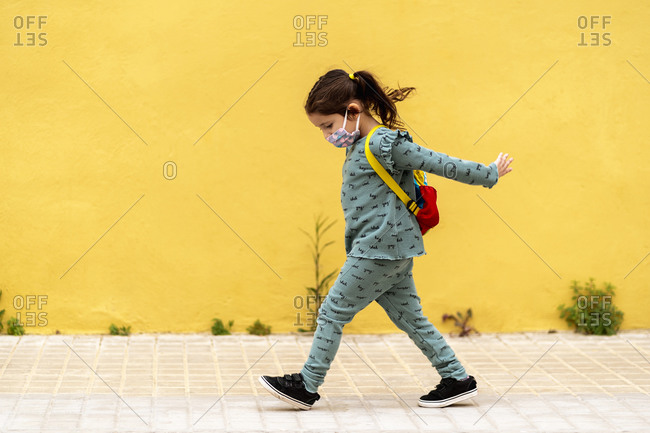 girl walking with backpack and mask outdoors