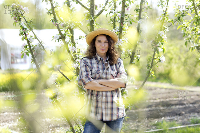 Portrait of confident mature female farmer standing with arms crossed at community garden