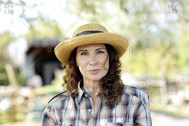 Portrait of confident mature woman wearing sun hat standing at community garden