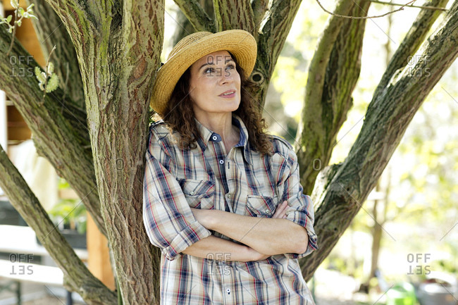 Thoughtful mature female farmer with arms crossed looking up while leaning on tree trunk at community garden