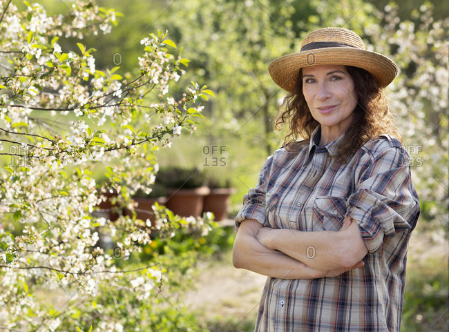 Portrait of smiling mature female farmer standing with arms crossed by tree at community garden