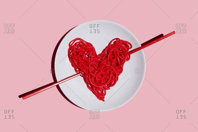 Studio shot of plate with red-colored heart-shaped spaghetti against pink background