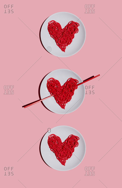 Studio shot of three plates with red-colored heart-shaped spaghetti against pink background