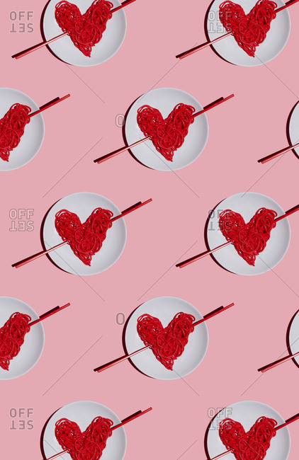 Pattern of plates with red-colored heart-shaped spaghetti against pink background