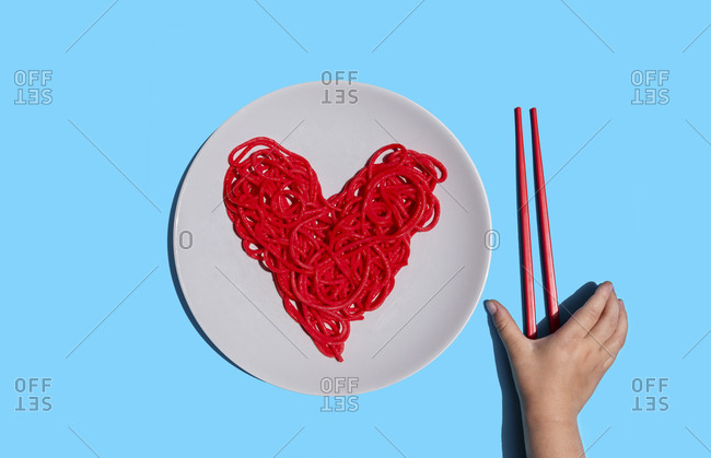 Hand of baby girl reaching for chopsticks to eat red-colored heart-shaped spaghetti