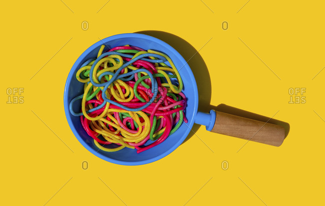 Studio shot of toy frying pan with colorful pasta