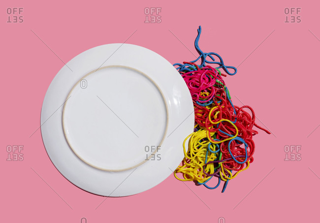 Studio shot of colorful pasta spilling from dropped plate