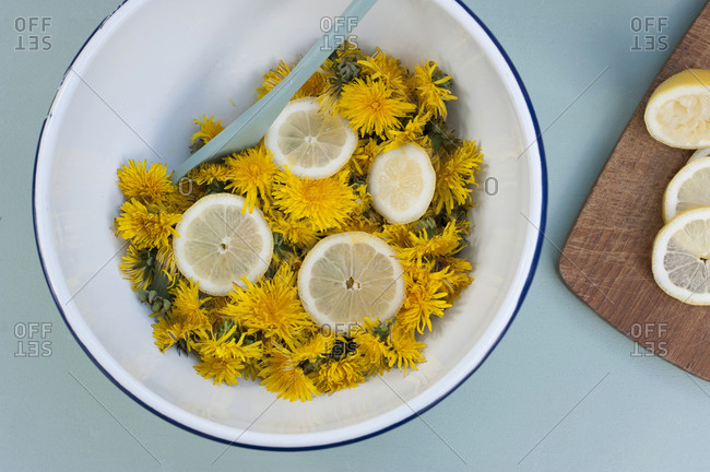 Germany- Bowl of dandelion heads with lemon slices