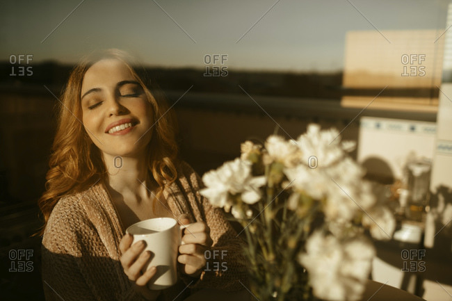 Happy blond woman at home drinking coffee in the kitchen in the morning