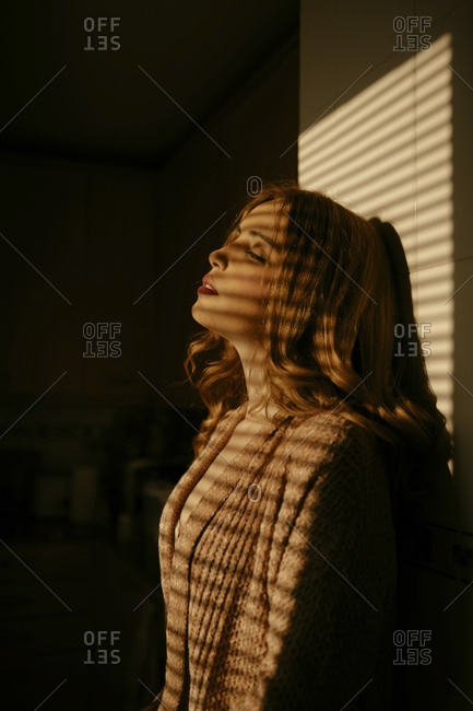 Portrait of beautiful blond woman at home in sunlight