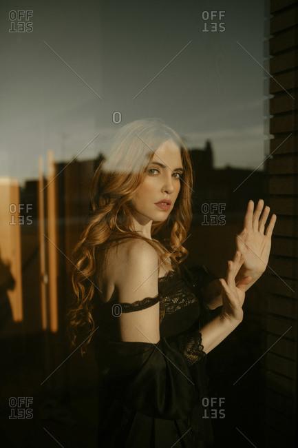 Portrait of beautiful blond woman in black lingerie behind windowpane
