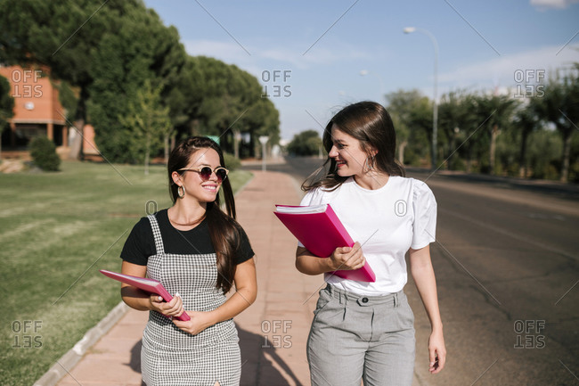 Happy female university students talking while walking on footpath at campus on sunny day