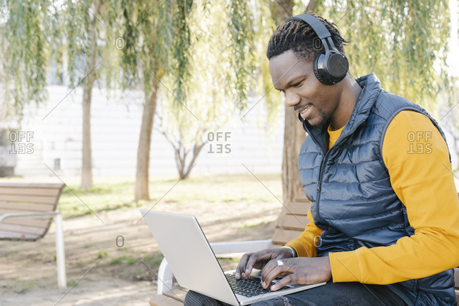 Young man with headphones sitting on park bench using laptop