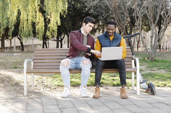 Two young men sitting on park bench sharing laptop