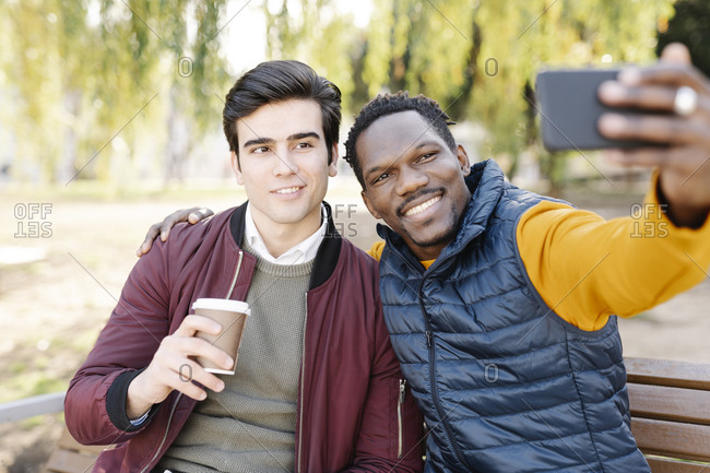 Two happy young men sitting on park bench taking a selfie