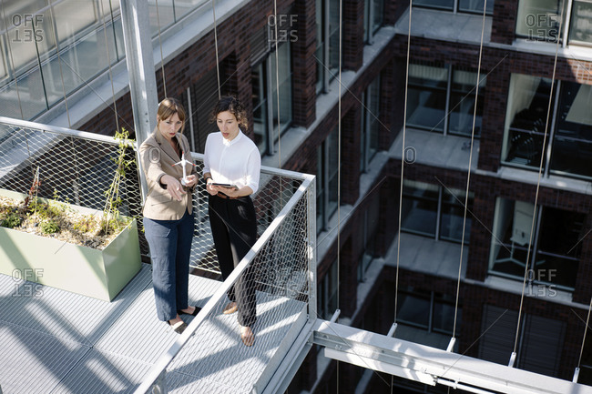 Two businesswomen with tablet and wind turbine model having a meeting on balcony of an office building