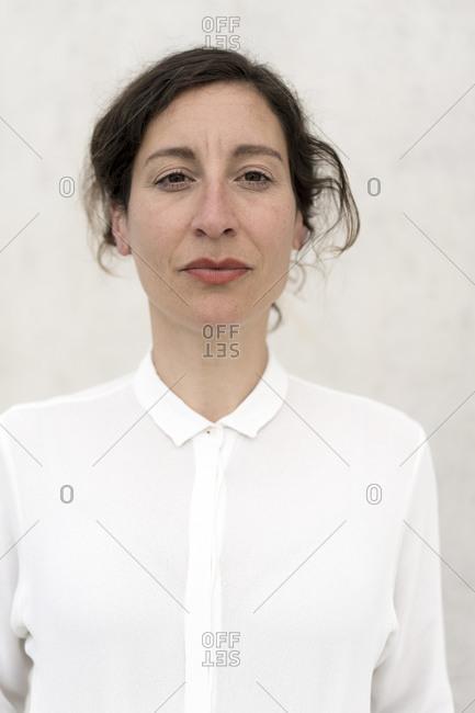 Portrait of a confident businesswoman at a concrete wall