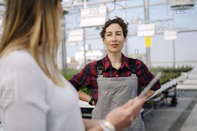 Gardener looking at businesswoman in greenhouse of a gardening shop
