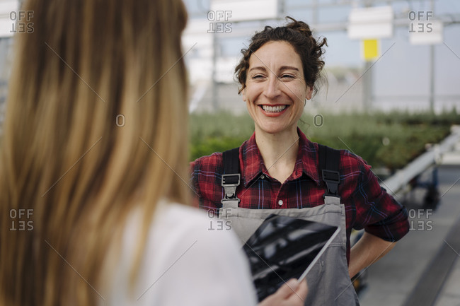 Smiling gardener looking at businesswoman in greenhouse of a gardening shop