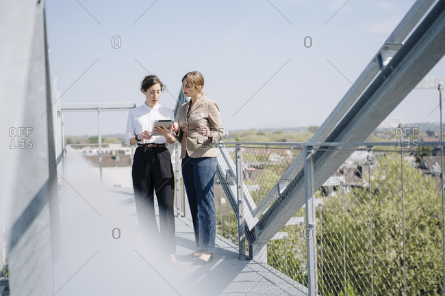 Two businesswomen with tablet having a meeting on roof terrace