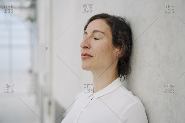 Portrait of a businesswoman with closed eyes leaning against a concrete wall
