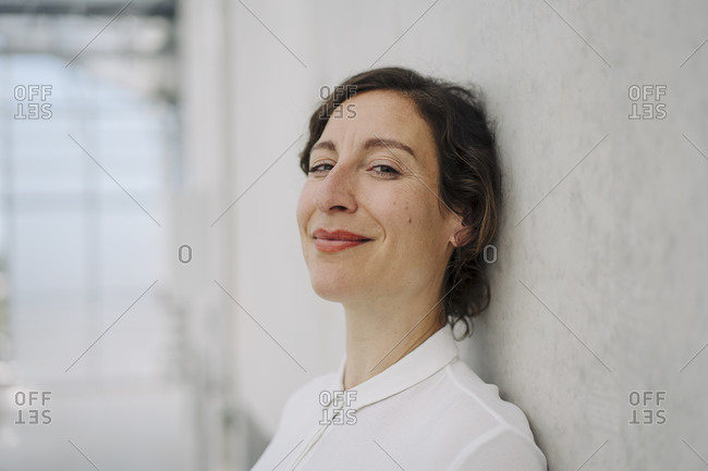 Portrait of a smiling businesswoman at a concrete wall