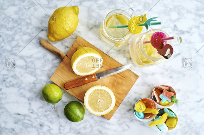 Cutting board- kitchen knife- lemons- limes- gummy candies and jars of fresh homemade lemonade