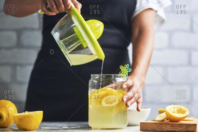 Hands of woman preparing fresh lemonade